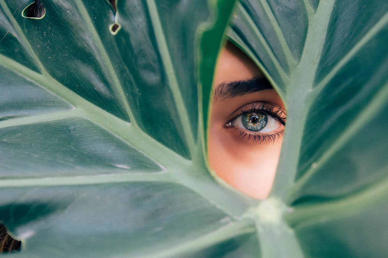 vrouw kijkt met oog door opening in blad